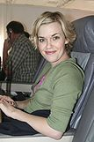 A woman sits in an airplane seat, smiling towards the camera. She has short blond hair.