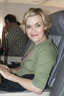 A blonde-haired young woman sitting in an airplane seat in a green top smiling at the camera.