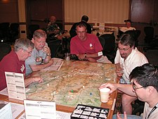 Five men sit at a table, poring over a map.  Dice and counters lie atop the map, some counters are stacked.  The map is subdivided into small hexagons of identical size.