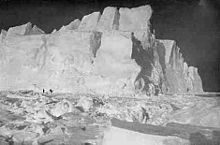 High cliffs of an iceberg set in broken pack ice