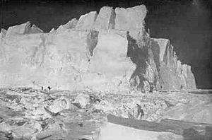 High cliffs of an iceberg set in broken pack ice