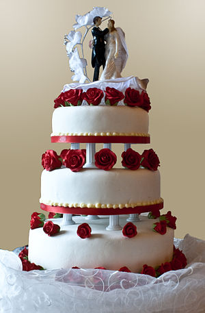 """Wedding cake - A three-layer wedding cake with pillar supports and """"topper"""" figures"""