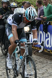 A road racing cyclist wearing a black and white jersey with pale blue trim, riding with his head down. A motorbike follows behind him, and spectators watch on from behind roadside barricades.