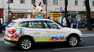 2012 Winter Youth Olympics - A BMW car with the Innsbruck 2012 logo while the mascot for the games looks on.