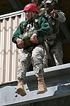 With the help of Sgt. 1st Class Donshay Morning, 6th Engineer Battalion, Colony High School Junior ROTC Cadet James Sawyer, 17, exits the 34-foot jump tower.jpg