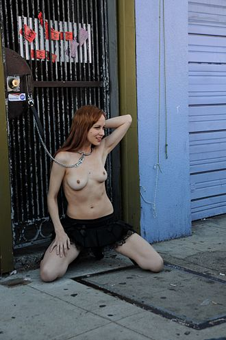 """Gorean subculture - Sexual roleplayer in a kajira pose at Folsom Street Fair. The woman is posing in an approximation to nadu, the typical position of a """"pleasure slave""""."""