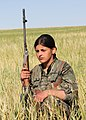 YPJ fighter squats in a field with her rifle.jpg