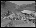 """A group of workers in front of the partially constructed warehouse just below the site of Norris Dam. The cement... - NARA - 532789.tif"