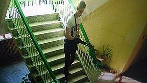Подозреваемый Владислав Росляков, вооружённый ружьём, спускается по лестнице в здании колледжа. Съёмка камеры видеонаблюдения, 17 октября 2018 года