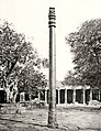1872 photograph of the Hindu Iron Pillar, from the Qutb complex west, colonnade of the Quwwat-ul-Islam Mosque in the background.jpg