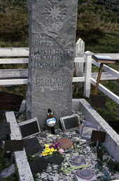 "A tall stone column stands over a grave on which rest various memorabilia including a bunch of flowers. The stone is inscribed: ""Ernest Henry Shackleton, Explorer, Born 15th February 1874. Died 5th January 1922""."