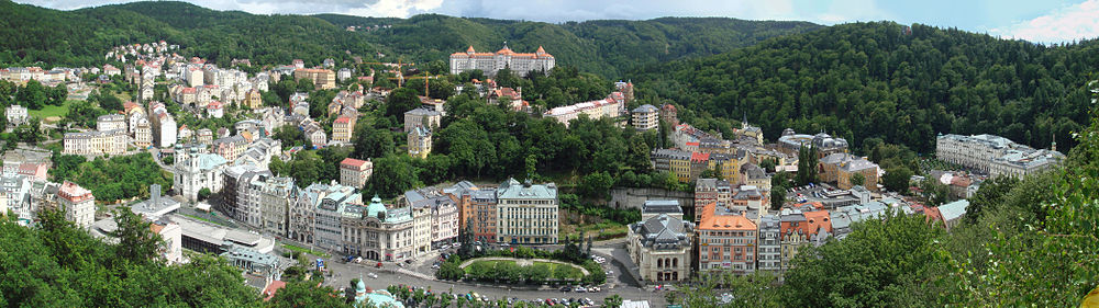 A significant portion of the spa/historic section of Karlovy Vary is shown. Major sites in photo, from left to right, are: The dark grey, socialist-era Thermal Spring Colonnade (also called Hot Spring Colonnade or Sprudel) features a glass chimney. Directly above it sits the twin-steeple Church of St. Mary Magdalene. The large, stately building on the center hill is the Hotel Imperial. Below it, to the right of the square, is the Opera House. The Grandhotel Pupp is the large white building to the far right.