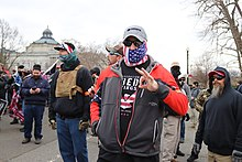 A participant in the 2021 storming of the United States Capitol uses the OK gesture.