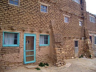 Acoma Pueblo - A buttressed three-story building, and a relic of the ancient 11th century brick architecture that still remain in small numbers on the Pueblo