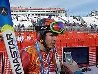 A man wearing skiing gear, being interviewed.
