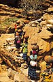 ASC Leiden - W.E.A. van Beek Collection - Dogon daily life 05 - Women climb the rock slope with pots of beer on the head on the path to the market in Sangha, Tireli, Mali 1990.jpg