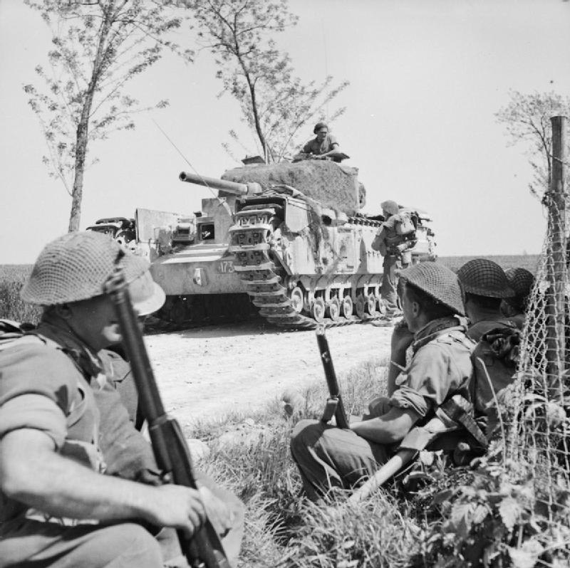 A Churchill tank halts near infantry of the 1st London Irish Rifles near Tanara during the advance to the River Po, Italy, 23 April 1945. NA24460