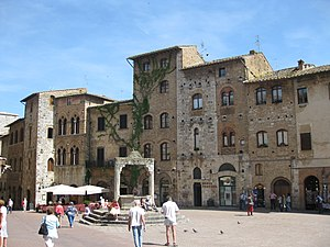 Romanesque secular and domestic architecture - Medieval buildings surrounding the Piazza della Cisterna in San Gimignano include a Romanesque building with an automated telling machine set into its portal.