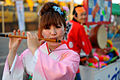 A young Japanese girl in traditional outfit playingg flute during festival. Fukuoka, Japan, East Asia.jpg