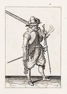 A pen and ink drawing of a soldier with a large musket over his shoulder.  He wears elaborate 16th century clothing including puffy knee breeches and a wide brimmed, tall hat with a plume.
