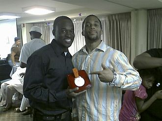 Trinidad and Tobago at the 2008 Summer Olympics - Aaron Armstrong (left) holding the silver medal he was originally awarded for his participation in the 4×100 meters relay