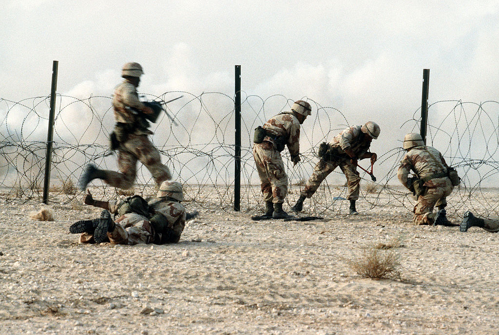 1024px-American_soldier_in_Iraq_going_through_concertina_wire.jpg