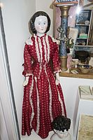 Antique china doll in red dress (26477189291).jpg