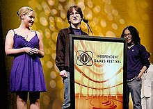 Two men stand behind a podium marked Independent Games Festival, while a woman in a blue dress stands to the left.