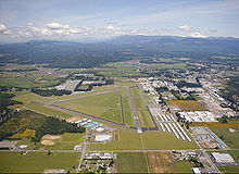 An airport with three angular runways, surrounded by hangars, warehouses, and open grass fields. Mountains and forestland can be seen in the background.