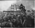 "As against ""The Shores of Tripoli"" in the Marine Hymn, Leathernecks use scaling ladders to storm ashore at Inchon in... - NARA - 532404.tif"