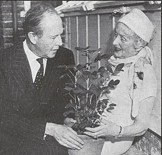 Atomic gardening - Former Atomic Gardening Society President Muriel Howorth shows popular garden writer Beverley Nichols a two-foot-high peanut plant grown from an irradiated nut in her own backyard.