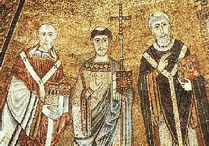 Mosaic image of three men dressed in elaborate robes. The central figure has a tonsure and is holding a cross-topped staff and closed book in one hand and his other hand is held upright, palm out. The left figure is bald and holds a model of a church in both hands. The right figure is tonsured and holds a book in one hand and makes a gesture with his other hand.