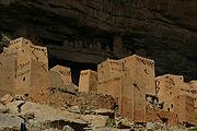 rektangulära lerahus (råjord) framför en brant klippa
