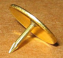 A brass tack with point downward