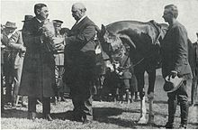 W.R. Brown accepting a silver bowl from another man, with a horse and its rider, dismounted, standing to the right