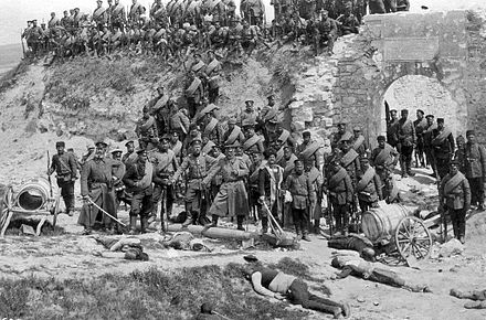Bulgarian soldiers in the Ayvaz Baba fort, outside Adrianople, after its capture. Bulgarian soldiers with dead Turkish civilians (Edirne).jpg