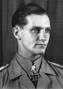 The head and shoulders of a young man, shown in semi-profile. He wears a military uniform with an Iron Cross displayed at the front of his white shirt collar. His hair appears blond and short and combed back, his nose is long and straight, and his facial expression is determined; looking to the left of the camera.