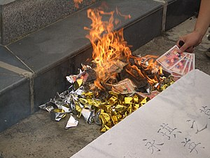 Hell money - Joss paper money being burnt near a grave along with joss yuanbao.
