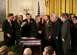 George W. Bush shakes hands with U.S. Senator Arlen Specter after signing H.R. 3199, the USA PATRIOT Improvement and Reauthorization Act of 2005