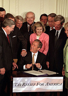 U.S. President George W. Bush signs a bill into law at a public ceremony.