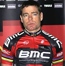 A man in his mid thirties wearing a black and red cycling jersey with white trim, and notable rainbow stripes around the biceps.