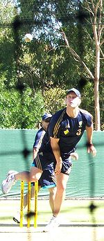 A man wearing dark blue cricket training kit with gold piping bowls a cricket ball. A net can be seen predominately in the fore-ground.
