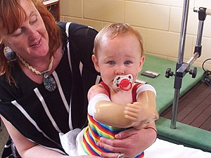 Charlotte Cleverley-Bisman - With mother Pam Cleverley, showing prosthetic arms and rehabilitation equipment.