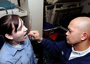 Genealogical DNA test - A hospital corpsman uses a swab to take a DNA sample from a sailor aboard USS Iwo Jima (LHD 7)