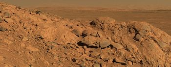 Fotografia tirada pelo rover Spirit a partir de um pequeno rochedo no meio da cratera Gusev que mostra a planície interior da cratera e a respectiva parede ao fundo, no horizonte.