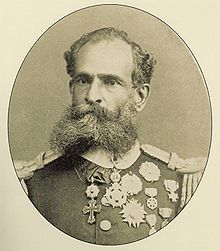 A photographic portrait of a dark-bearded man in heavily braided military tunic bedecked with many medals.