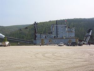 Profile view of above dredge tied up to a quay, note the size. The dredge conveys the spoils to the rear (left side) into a receiving vessel such as a barge.