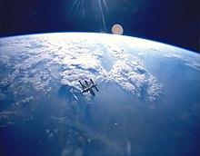 Shluk modulů a opeřených solárních polí plave ve střední vzdálenosti před obrazem Země a temnotou vesmíru nad jejím horizontem.  Sluneční paprsky se promítají z horního středu obrazu.