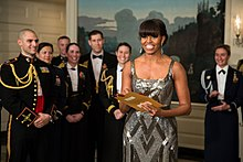 An African-American female in her late forties is seen wearing a silver dress and holding a golden envelope. Several men and women wearing black military garb are standing behind her.