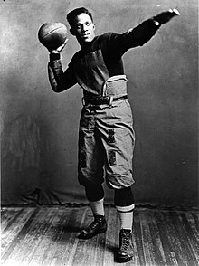 Pollard in football uniform staring off in the distance and striking a classic football pose; one arm is outstretched, while the other holds a football, as if he were about to throw it.
